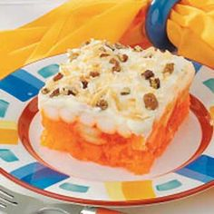 Frosted Orange Salad - Pineapple, bananas and marshmallows are folded into orange Jell-O in this refreshing salad. Frosted with a creamy topping, pecans and coconut.
