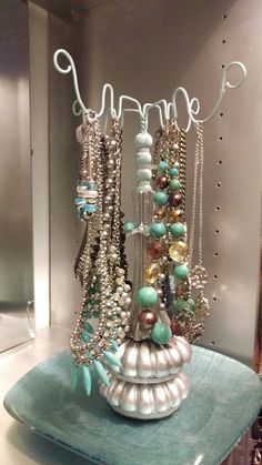 Small closet makeover. Jewelry hanger for necklaces and bracelets. Made from two table feet, a vase, wooden balls, coat hangers, hot glue and paint.