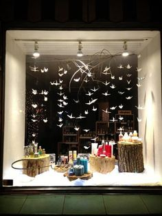 (A través de CASA REINAL) >>>> This is Cila salon window display. Merchandiser put the products on the different size, and colour logs. And fake snow powder is on all the bottom. There are bunch of paper cranes, it looks like they are falling down like snow. Three lights are strong enought to show their products.
