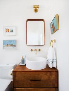 Nautical inspired bathroom with a brass details, a worn wooden cabinet, and a round white porcelain sink
