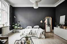 This Swedish studio apartment from My Scandinavian Home beautifully juxtaposes a sense of glam and effortlessness: It's all at once casual and luxurious, with its rumpled linen beddings and ornate moldings and mirror. The satin black walls come across soft and inviting.