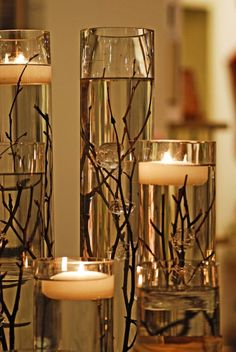 Dollar store vases, branches, water, and floating candles. Add in some gold metallic to the branches