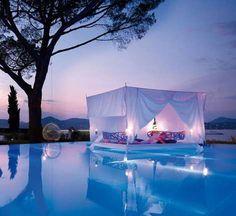 Chambre à coucher : le lit à baldaquin XXL au bord de la piscine