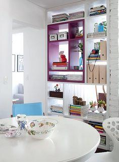 Em vez de ocupar espaço, a estante pode ficar no lugar de uma parede, como no apartamento de 70 m² da arquiteta Marcela Madureira. Ela faz a divisão entre o living e a sala de TV e tem uma parte magenta para dar um toque de cor à decoração