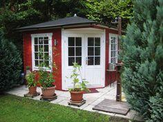 Inmitten von Grün steht dieses süße Gartenhaus in Weiß und Schwedenrot. Pflanzkübel auf der kleinen Terrasse machen die Gartenidylle perfekt.