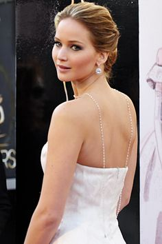 Jennifer Lawrence is dripping in Chopard! Here she pairs her white Dior Haute Couture gown with pear-shaped diamond cluster earrings, two diamond rings, and a whopping 74 carat diamond bead chain, which she's draped down her back. #Oscars2013