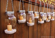 mason jar lanterns hanging from a fence