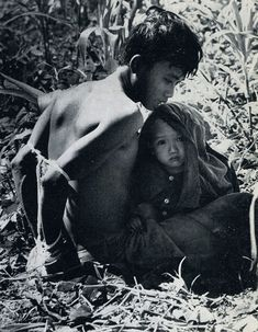 A suspected Viet Cong sits with his child awaiting interogation - photo by Rick Merron, USA ~ Vietnam War