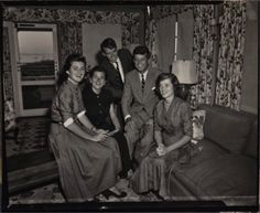 John F. Kennedy and siblings Jean, Patricia, Bobby, and Eunice looking over campaign material in Hyannis Port.