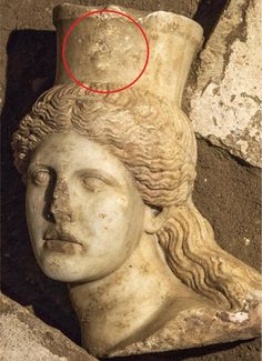 Beautiful: Archaeologists have found a female head belonging to a headless sphinx discovered at a mysterious Alexander the Great-era tomb in north Greece. The head has tumbling curls, (pictured) which they say were once painted a red colour