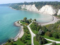 """Scarborough Bluffs - Forming much of the eastern portion of Toronto's waterfront, the Scarborough Bluffs has been described as a """"geological wonder"""" and a unique feature in North America. The bluffs were named after Scarborough, England by Elizabeth Simcoe, the wife of John Graves Simcoe, the first lieutenant governor of Upper Canada. The bluffs run 14 kilometres from the foot of Victoria Park Avenue in the west to the mouth of Highland Creek in the east, reaching as high seventeen storeys."""