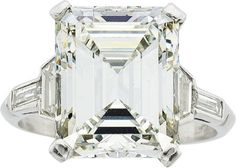 The ring features an emerald-cut diamond measuring 13.42 x 10.66 x 7.06 mm and weighing 8.76 carats, enhanced by trapezoid-shaped diamonds weighing a total of approximately 0.50 carat, accented by baguette-cut diamonds weighing a total of approximately 0.10 carat, set in platinum