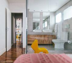Banheiro integrado ao quarto com bancada de concreto e marcenaria feita com Teca.