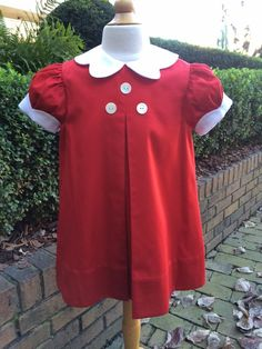 Red Swiss gabardine apron dress with white Swiss sateen hand-scalloped collar and cuffs with Mother of Pearl button detail on bodice. McCall Wilder Couture for Children.