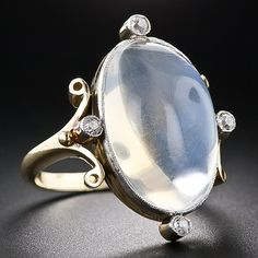 Antique Moonstone and Diamond Ring - A shimmering and sizable 12 Carat translucent moonstone is the compelling centerpiece of this enchanting hand-fabricated platinum and gold late-nineteenth/early-twentieth century ring. At points north, south, east and west, four mine-cut diamonds lend their starlit twinkle to the moonlit glow. Measures 1 inch long by 3/4 inch wide.