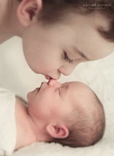 Brother giving a kiss to baby