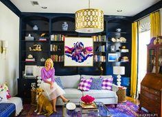 Ceiling-to-floor rich navy shelving and a mahogany secretary add warmth and storage, while an overdyed floor rug and gold pendant light strike a playful contrast. Guests seated on the vivid blue chaise have a prime view of the room's focal point: a stunning abstract painting.