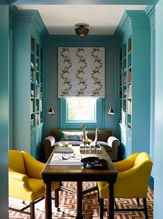 Create an inviting and inspiring library space with floor to ceiling turquoise painted walls and bookshelves paired with bold and comfortable yellow arm chairs.