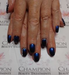 A dry manicure complete with CND Shellac 'Blackpool' nail polish. 'Blue' Mica Additive was used to create an ombre effect. Silver rhinestones have been added to both ring fingers.