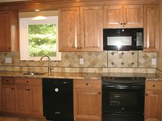 Compact kitchen has cherry cabinets in a shaker style, stainless range hood with spice rack, slide in gas range and pot filler