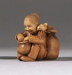 """WOOD NETSUKE Contemporary By Susan Wright. Depicting a seated woman with grain sack and basket being observed by a bird perched on her shoulder. Signed on gold inlaid plaque. Length 1.6"""" (4 cm)."""