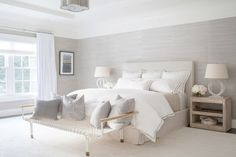 The master bedroom is awash in creamy hues and features luxurious details like grasscloth wallpaper from Phillip Jeffries and alabaster lamps from Circa Lighting. A linen-cotton weave fabric covers the bespoke platform bed, while a cotton rope cot from Anthropologie is used as a bench.