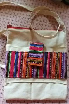 Bolsinha tiracolo em algodão cru. Detalhes em lã peruana legítima.