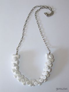 Many beads of white cotton fabric and a silver chain create a necklace original and easy to wear!
