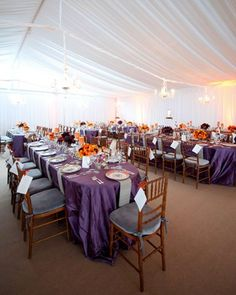 (Currie Wedding)  The main wedding colors of eggplant, deep orange, and slate gray filled the tent, which was draped in white fabric and vintage-style chandeliers. Custom silk dupioni tablecloths with gray cotton napkins covered the two long tables that connected with half rounds at each end. Fruitwood reception chairs with gray cushions rounded out the romantic look.