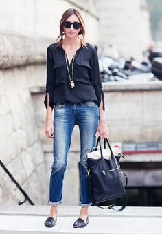 Straight leg jeans worn with a silky black top and a gold statement necklace
