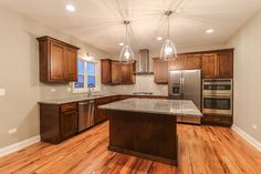 Custom gourmet kitchen with stainless steel appliances and dark stained custom maple cabinets.