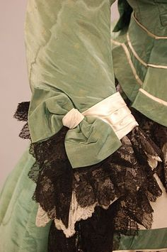 A green watered silk formal gown, circa 1865, the  Sign In to see what this sold for  A green watered silk formal gown, circa 1865, the lightly padded bodice trimmed with cream and black lace and bows