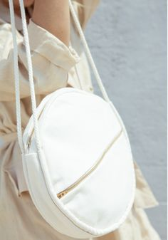 "Serus cotton canvas bag. Features rope handles, one exterior pocket, and a  zipper closure. Natural color and brass zipper (right). 10"" diameter; 19.5""  drop from shoulder to top of bag. Made in the USAQuestions about this  product? Email help@lisasaysgah.com"