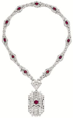Ruby and diamond pendant necklace.    The pendant centring on an oval ruby, to a stylised openwork surround set with baguette and brilliant-cut diamonds, to a necklace set with oval rubies and variously-cut diamonds, the rubies and diamonds together weighing approximately 11.50 and 20.00 carats respectively, mounted in 18 karat white gold, length approximately 460mm, pendant detachable and with brooch fitting. Via Sotheby's.
