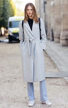Sanne Vloet wears a black top, long waisted wool coat, jeans, and white sneakers