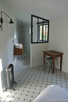 Voilà une jolie salle de bains à la forme atypique ! On adore son sol en en carreaux de ciment et sa verrière d'intérieur...                                                                                                                                                                                 Plus