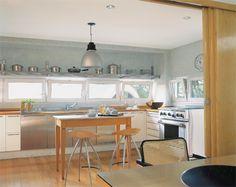 pastilhas de vidro branco-gelo nas paredes e piso de madeira tauari, protegida com sinteco. Se a porta de marfim, com seis folhas de correr, fica aberta, a sala de jantar se transforma na extensão da cozinha.