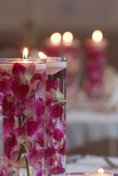 reception decor - table decor - centerpiece - cylindrical glass vases with submerged dendrobium orchids and floating candles