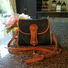 "Vintage Dooney & Bourke Crossbody vintage Essex style bag.  Black pebble with brown leather trim, gold hardware and buckle style closure.  Length 9.5"" Height 8.5 Dooney & Bourke Bags Crossbody Bags"
