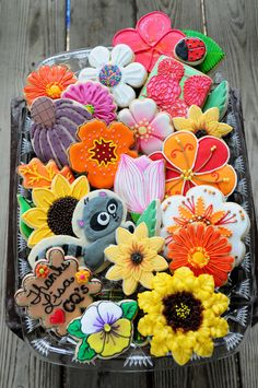 An absolutely gorgeous array of spring/summer garden themed flowers Cookies - complete with the most adorable raccoon cookie ever!