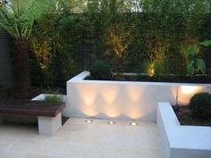 Chic Little Courtyard Raised beds and bench with limestone paving. Bamboo uplit at night