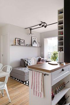 Decoração de apartamento que mistura estilos, mas com predomínio do estilo escandinavo, com uma base branca e leve. Na sala sofá cinza, tapete preto e branco, móvel de madeira e branco, quadros e luz natural. Na cozinha, cadeiras brancas, mesa branca e móvel de madeira e branco.