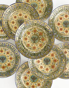 A Set of Ten Russian Dessert Plates from the Kremlin Service, Imperial Porcelain Manufactory, St. Petersburg, Period of Nicholas I (1825-1855) the cavettos painted with the black double-headed Imperial Eagle with crown, orb and sceptre on a green ground, enclosed within a gilt band inscribed in Russian 'Nicholas, Emperor and Autocrat of All the Russias,' surrounded by vermilion rosettes and foliate ornament on a richly gilded ground