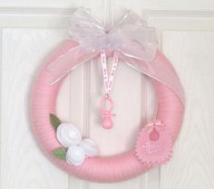 """This pink yarn wreath is a beautiful way to announce It's a Girl! Use for baby shower decoration or a gift for the mother to be. Hang as a pretty welcome home for that special baby girl. 12"""" pink yarn wreath with handmade felt flowers and material bib which has """"Baby Girl"""" printed on it. A pink plastic pacifier hangs down the center of the wreath on """"It's A Girl"""" printed ribbon. White organza handmade bow has iridescent trim. A beautiful keepsake for baby!"""