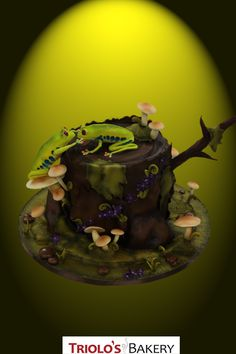 Two life like, hand sculpted frogs sit atop a realistic tree stump made of cake. This magical forest themed wedding cake also features handmade and edible pebbles, flowers, moss, and mushrooms.