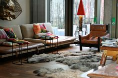 so interesting...wall sculpture, fur rugs, pops of color and still manages to be relatively neutral