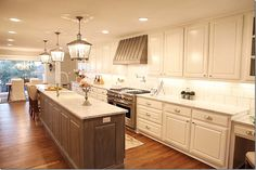 Love the colors used in this kitchen and the contrast between the island and white cabinets. Really like the color of the hardwood floors.
