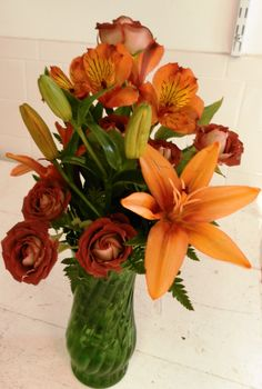 This lily looks like the sun!! Tangerine lilies, merlot spray roses and yellow-orange alstromeria create this medium arrangement.