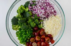 Glass bowl containing diced red onion, hredded mozzarella cheese, halved red grapes, chopped scallions and broccoli florets.
