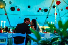 Kissing at their reception with lots of hanging lanterns in the tent